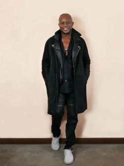 David Sancious standing against wall in leather jacket